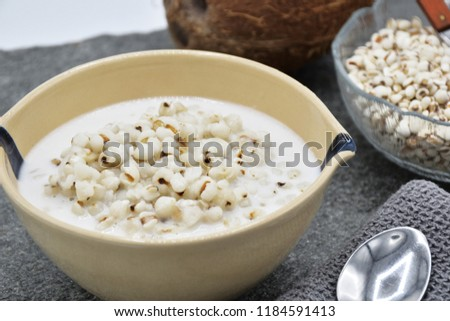 Job's tears seeds cook in the coconut milk in the bowl. The healthy food concept. The seeds are rich in minerals, vitamins, dietary fiber, and essential amino acids. selective focus. Thai dessert. #1184591413