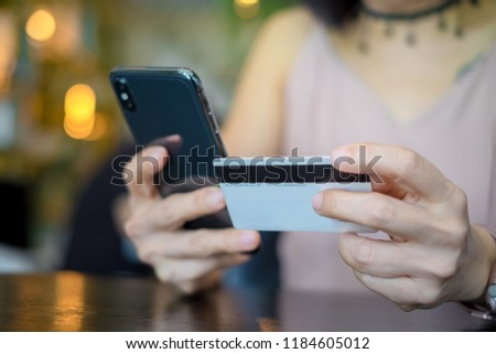 Young woman holding credit card and using smartphone. Online shopping concept #1184605012