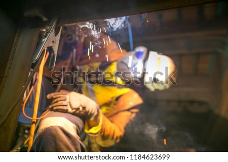 Pic of earth ground welding equipment clamp on the wall with blurry rope access welder working at height ascending abseiling performing welding at the background construction site Sydney, Australia