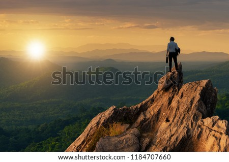 Concept vision, Young businessman wearing comfortable casual suit jacket standing holding business bag on top of peak mountain and looking forwards, success, competition and leader concept. #1184707660