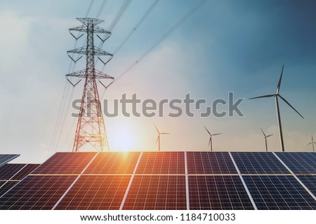 Solar panels with electricity pylon and wind turbine Clean power energy concept. sunset background #1184710033