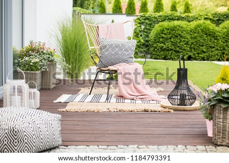 Real photo of a white pillow and pink blanket on a rattan chair standing in the garden of a luxurious house #1184793391