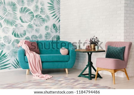Real photo of bright sitting room interior with wooden end table with fresh plant and two mugs standing between dirty pink armchair and turquoise lounge with pillows and blanket #1184794486