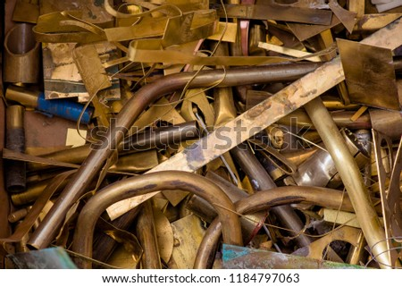 yellow metal from brass. remnants of brass processing after punching. Textural background. brass details close-up Royalty-Free Stock Photo #1184797063