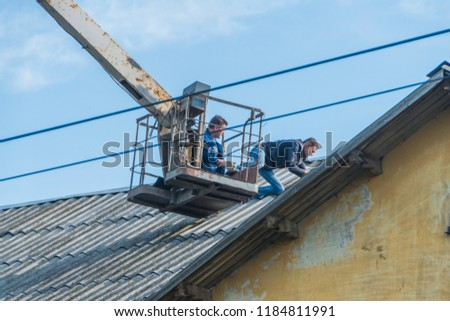 Russia, Leningrad region, Nikolskoe, 20 Sep 2018 - the roof repair shingles, slate with aerial platforms. #1184811991