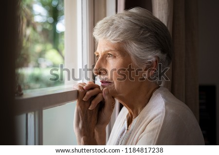 Depressed senior woman at home feeling sad. Elderly woman looks sadly outside the window. Depressed lonely lady standing alone and looking through the window. #1184817238