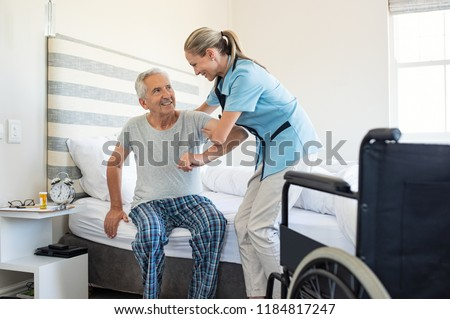 Smiling nurse assisting senior man to get up from bed. Caring nurse supporting patient while getting up from bed and move towards wheelchair at home. Helping elderly disabled man standing up. #1184817247