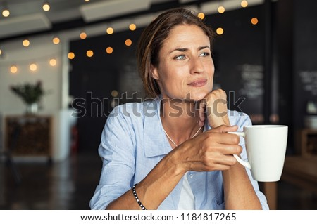 Thoughtful mature woman sitting in cafeteria holding coffee mug while looking away. Middle aged woman drinking tea while thinking. Relaxing and thinking while drinking coffee. #1184817265
