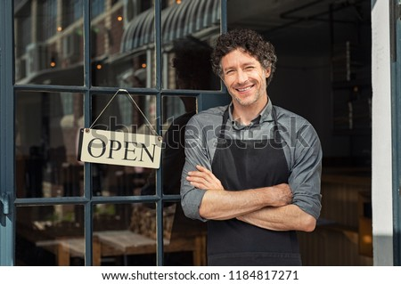 Portrait of small business owner smiling and standing with crossed arms outside the cafe. Portrait of handsome mature waiter standing in entrance of coffee shop.  #1184817271