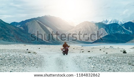 Tourist riding an adventure big bike motorcycle on tuff and bumpy road on rock mountain in clear beautiful lightning to explore the world, with copy space  #1184832862