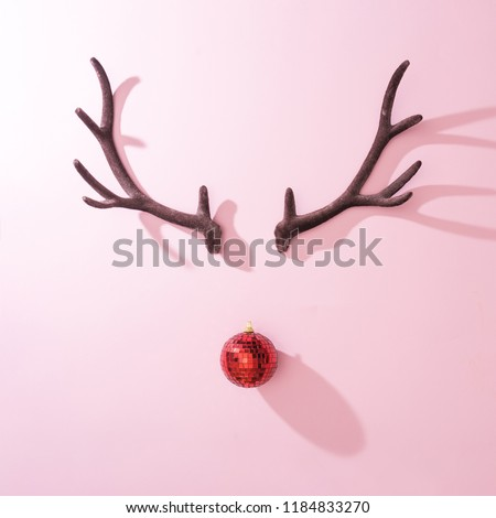 Red Christmas disco ball bauble with reindeer antlers on pink background. Minimal New year Santa concept. Flat lay. #1184833270