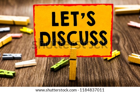 Conceptual hand writing showing Let s is Discuss. Business photo showcasing Permit to Talk Open Up Go Over a Topic Chat Sharing Clothespin holding orange paper note clothespin wooden floor. Royalty-Free Stock Photo #1184837011