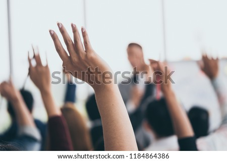 Audience raising hands up while businessman is speaking in training at the office. Royalty-Free Stock Photo #1184864386