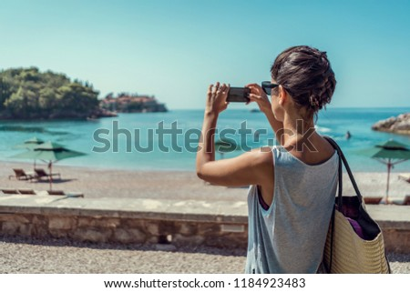 Beautiful female on vacation taking picture of beautiful beach with phone