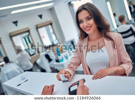 Attractive young woman is spending time in beauty salon. Paying via credit card.