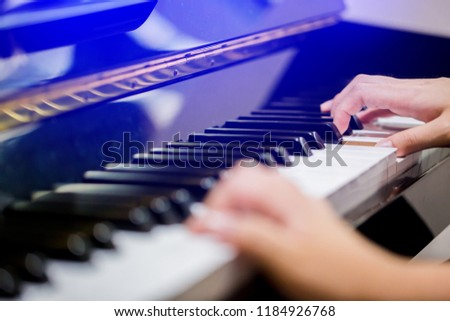 Selective focus to fingers of woman teaching boy to play the piano. Hands from two people playing piano with music notation. There are musical instrument for learning music. #1184926768