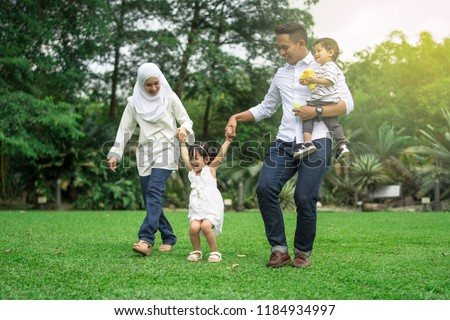 malay family having quality time in a park with morning mood #1184934997