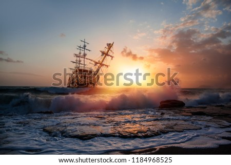 Sailing old ship in storm sea against dramatic sunset #1184968525