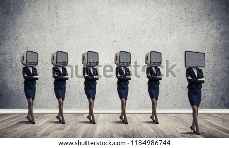 Businessmen in suits with old TV instead of their heads keeping arms crossed while standing in a row and one at the head with TV in empty room against gray wall on background. #1184986744