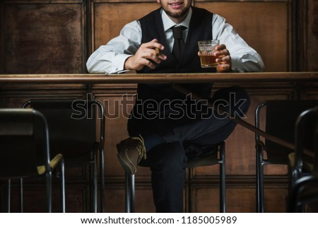 Man sits in the luxury bar in male gentlemen club and drinks alc #1185005989