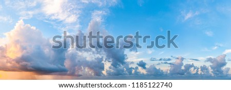 Twilight sunset with colorful clouds. Dramatic atmosphere created by the sunlight. Colorful gradient from blue to orange. Blue sky and clouds. High resolution panoramic sky. Royalty-Free Stock Photo #1185122740