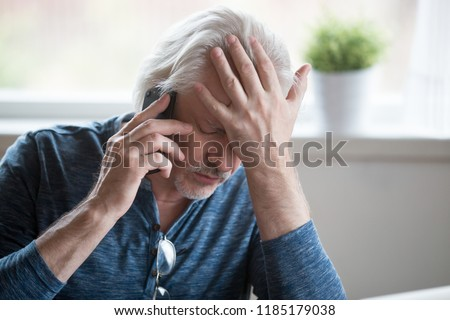 Frustrated older mature retired man feeling upset desperate talking on the phone having problems debt, stressed sad middle aged male depressed by hearing bad news during mobile conversation at home #1185179038