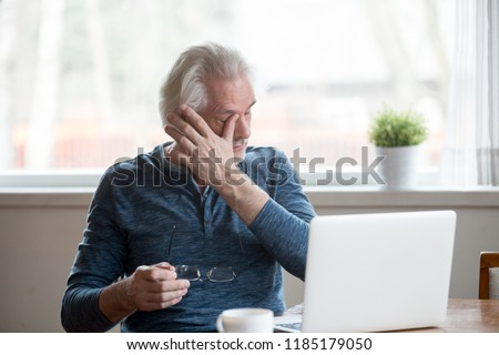 Fatigued mature old man taking off glasses suffering from tired dry irritated eyes after long computer use, senior middle aged male feels eye strain problem or blurry vision working on laptop at home #1185179050