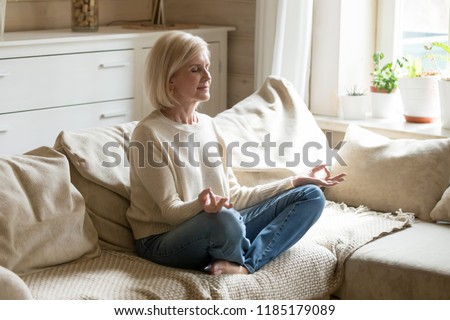 Mindful healthy mature woman practicing meditation at home, calm senior middle aged lady sitting on couch in lotus pose doing yoga for mental balance breathing air relaxing on stress free weekend #1185179089