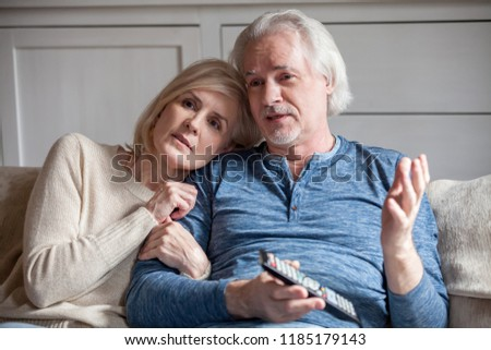 Serious middle aged senior couple embracing talking watching tv together at home, retired mature older family talking discussing television news with remote control sitting on sofa in living room #1185179143