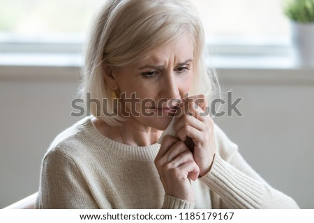 Upset middle aged woman wiping tears crying feeling depressed hopeless lonely after divorce, desperate old senior widow thinking of disease, sorrow or grief, mature elderly lady mourning concept #1185179167