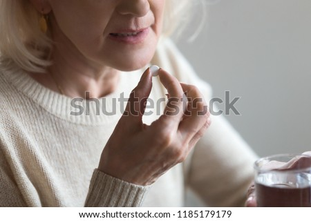 Mature senior middle aged woman holding pill and glass of water taking painkiller to relieve pain, medicine supplements vitamins, antibiotic medication, meds for old person concept, close up view #1185179179