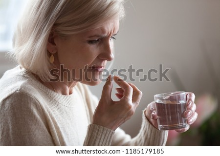 Upset senior ill woman holding pill and glass or water taking painkiller medicine to relieve headache pain, sad middle aged elderly lady worried about side effects of meds for old person concept #1185179185