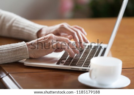 Mature female hands typing text on keyboard, senior elderly business woman working on laptop, old or middle aged lady using computer concept writing emails, communicating online, close up view #1185179188