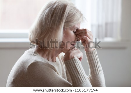 Fatigued upset middle aged older woman massaging nose bridge feeling eye strain or headache trying to relieve pain, sad senior mature lady exhausted depressed weary dizzy tired thinking of problems #1185179194