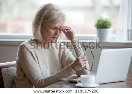 Upset fatigued overworked senior mature business woman taking off glasses tired of computer work, exhausted middle aged employee suffers from blurry vision after long laptop use, eye strain problem #1185179200