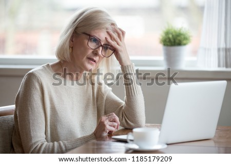 Thoughtful confused mature business woman concerned thinking about online problem looking at laptop, frustrated worried senior middle aged female reading bad email news, suffering from memory loss #1185179209