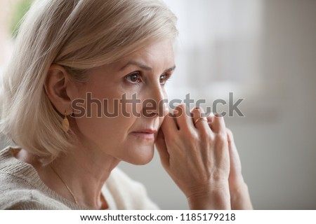Thoughtful serious anxious mature senior woman feeling blue worried about problems, pensive upset sad middle aged grey haired lady looking away thinking of loneliness, getting older and depression #1185179218