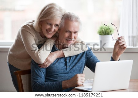 Senior middle aged happy couple embracing using laptop together, smiling elderly family reading news, shopping online at home, older people and computer or good vision after laser correction concept #1185179251