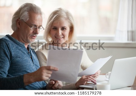 Happy old middle aged couple holding reading good news in document, smiling senior mature family excited by mail letter, checking paying domestic bills online on laptop, discussing budget planning #1185179278