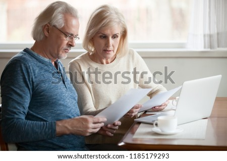 Serious worried senior couple calculating bills to pay or checking domestic finances stressed of debt, retired elderly old family reading documents concerned about loan bankruptcy money problems #1185179293