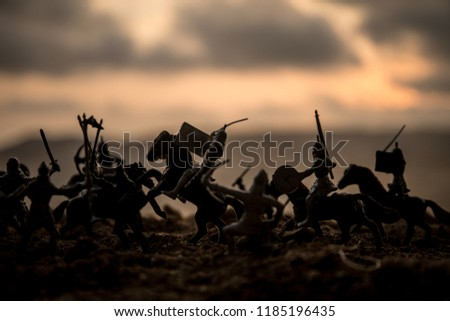 Medieval battle scene with cavalry and infantry. Silhouettes of figures as separate objects, fight between warriors on sunset foggy background. Selective focus #1185196435
