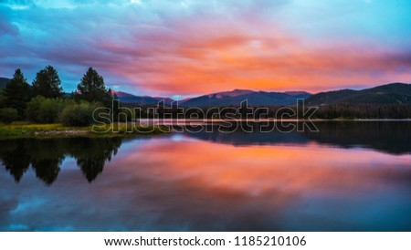 Orange skies at sunset reflected over mountain blue lake in high country. #1185210106