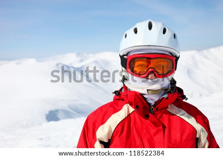 Closeup portrait of a female skier standing on a skiing slope #118522384