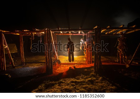 Horror view silhouette of hanged man on scaffold at night with fog and toned light on background. Execution (or suicide) decoration. Horror Halloween concept. #1185352600