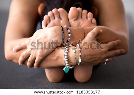 Young sporty woman practicing yoga, doing Seated forward bend, head to knee exercise, paschimottanasana pose, working out, wearing bracelets, indoor close up, at yoga studio #1185358177
