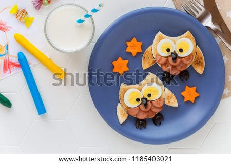 Fun food for kids - cute little owls shaped sandwiches or toasts with sausages and eggs. Overhead view  #1185403021