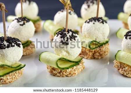 An unusual beautiful appetizing appetizer for a festive table. Mini canapes from a piece of baguette with sesame, thin slice of cucumber and a ball of cheese. Exotic black sesame for decoration. #1185448129