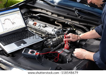 Professional car mechanic working in auto repair service. Royalty-Free Stock Photo #118548679