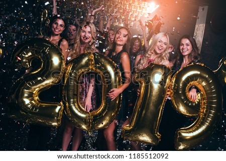 Happy new year! Beautiful young women in evening gown holding balloons and looking at camera with smile while celebrating in nightclub  #1185512092