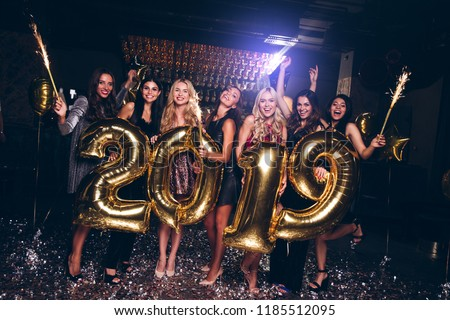 Happy new year! Beautiful young women in evening gown holding balloons and looking at camera with smile while celebrating in nightclub  #1185512095